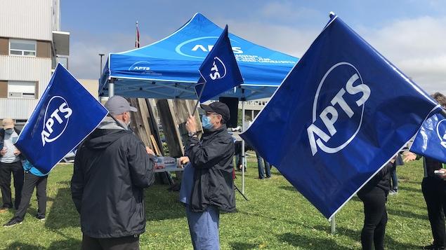 Cinq travailleurs membres de l'APTS ont des drapeaux aux couleurs du syndicat dans les mains et sont devant un chapiteau érigé pour l'occasion.