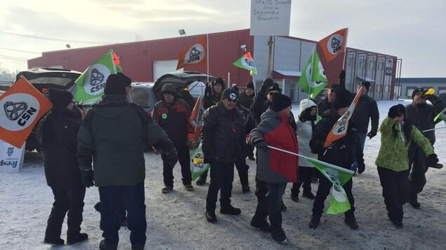 Gens avec des drapeaux de la CSN dehors.
