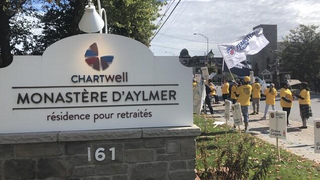 Des employés vêtus de chandails jaunes manifestent avec des drapeaux et des pancartes devant l'entrée de la résidence pour retraités Le Monastère