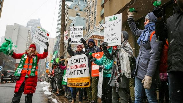 Ils manifestent sur le trottoir avec des pancartes.