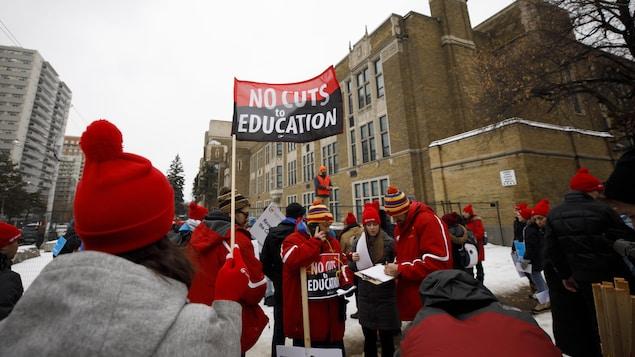 Des grévistes font du piquetage devant une école et dénoncent les compressions en éducation.