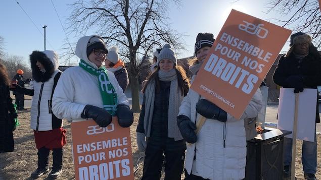 Des enseignants tiennent des pancartes.