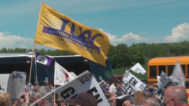 Des travailleurs en grève tiennent des pancartes et des drapeaux syndicaux dans les airs.