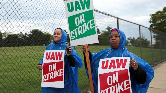Deux femmes brandissent des pancartes sur lesquelles on peut lire « En grève ».