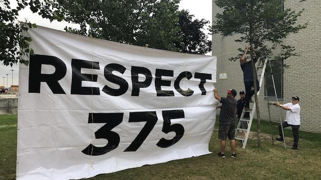 Des hommes accrochent une immense bannière sur laquelle on peut lire : Respect 375.