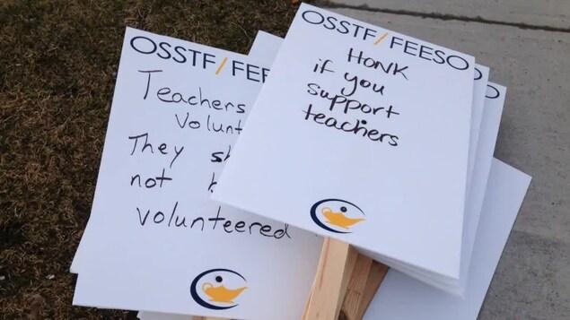 Des pancartes en anglais sont étalées sur un trottoir.