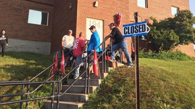 Des membres du syndicat Unifor devant la porte avec un écriteau indiquant que le centre est fermé.