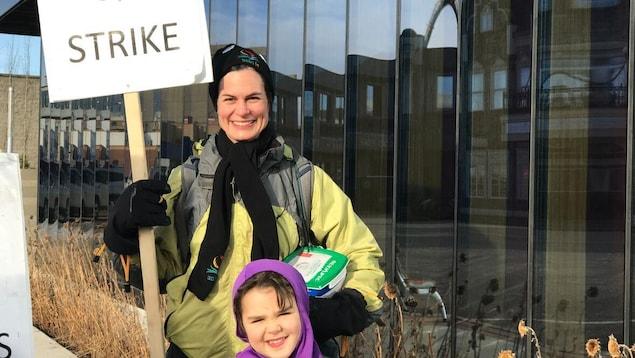 Un professeur et un enfant sur le piquet de grève d'une université.