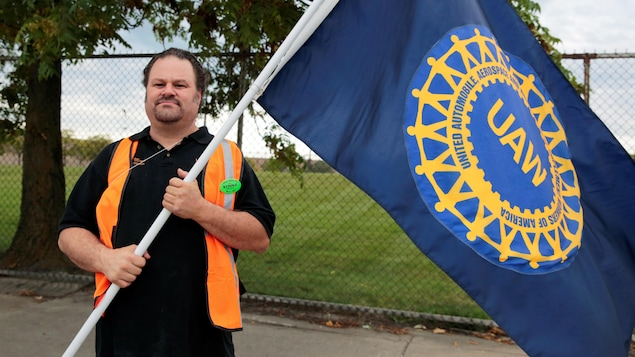 Un travailleur tient dans ses mains un grand drapeau du syndicat United Auto Workers