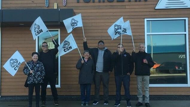 Des employés avec des drapeaux de la CSN devant les bureaux de Tshiuetin.