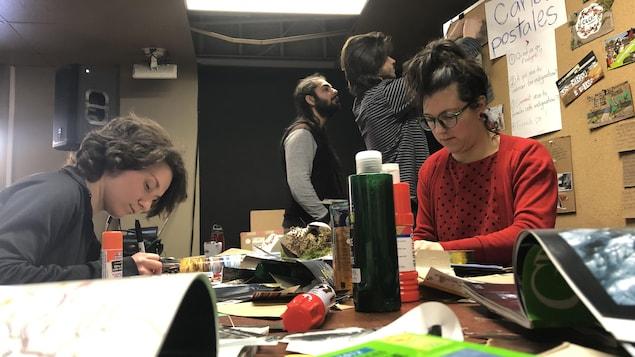 Quatre étudiants bricolent des cartes postales sur un bureau en désordre.