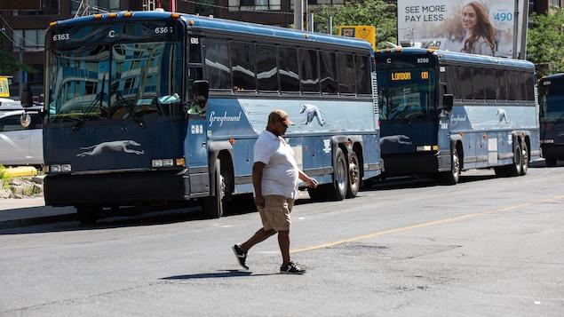 Un homme traverse la rue devant des autocars de Greyhound stationnés près du terminus de Toronto.