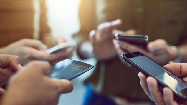 Une photo montrant un groupe de personnes en train d'utiliser leur cellulaire.