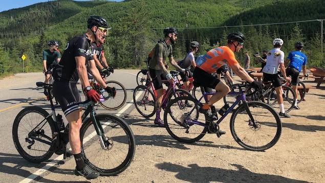 Des cyclistes quittent une route pour s'aventurer sur un chemin en gravier.