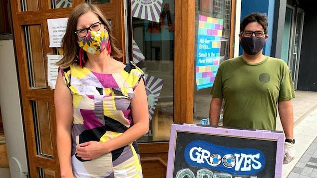 Deux personnes portent un masque sur un trottoir