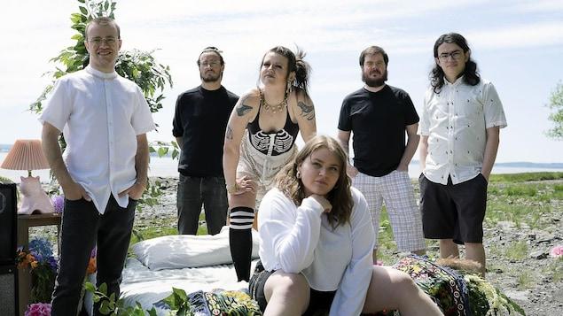 Six musiciens se tiennent dans un décor de chambre à coucher, placé dehors, sur le bord d'un cours d'eau.