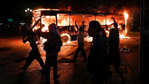 Des manifestants devant un autobus en feu.