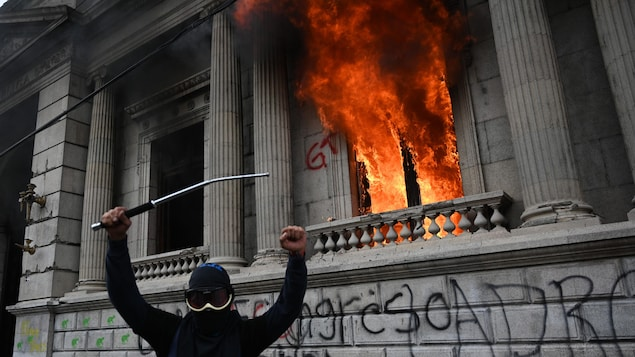 Un manifestant armé d'une barre de fer lève les bras en l'air devant un bâtiment en feu couvert de graffitis.