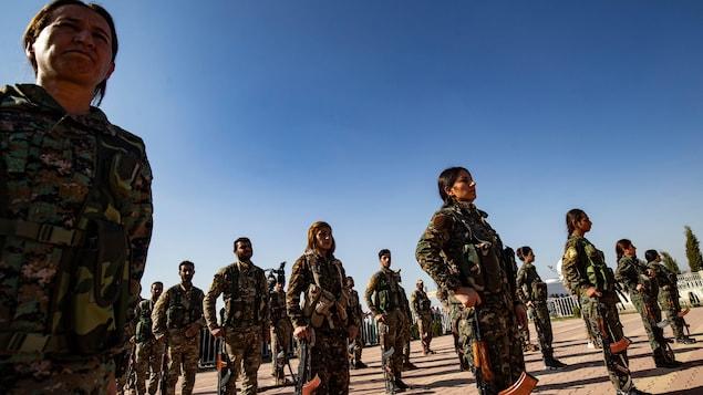 Des combattants kurdes en rangs ouverts, l'arme au pied.