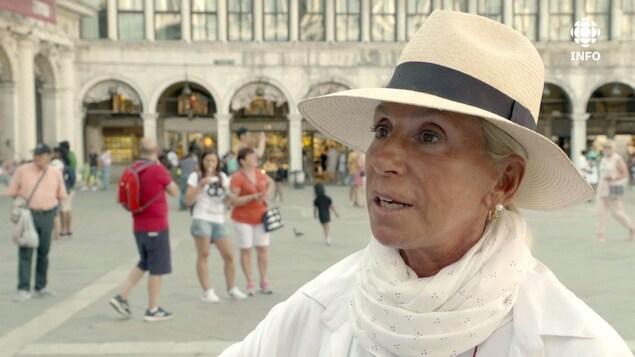 La guide touristique parle à la caméra sur la place Saint-Marc.