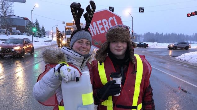 Mélanie Hainse et son fils Antoine posent dans la rue et tiennent une bouteille de dons.