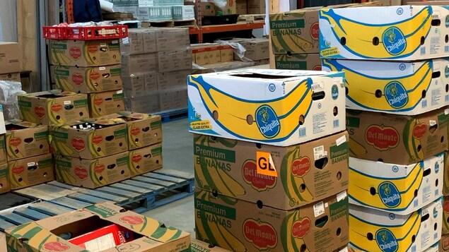 Des boîtes de cartons de denrées empilées dans un entrepôt.