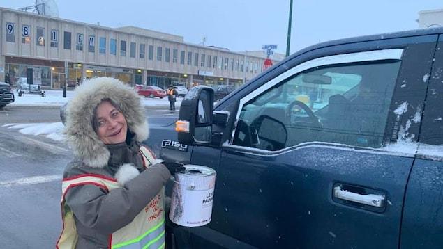 Une bénévole récolte des dons.