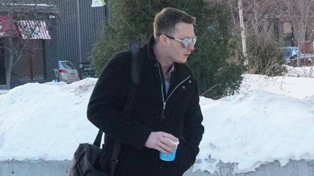 Le jeune homme porte des lunettes de soleil et tient un café dans sa main.