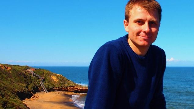 Portrait en couleur, en extérieur, de l'auteur Guillaume Reix au soleil, avec en arrière-plan une plage et la mer.