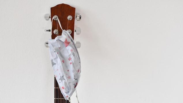 Un masque accroché à la tête d'une guitare dont on voit une partie du manche.