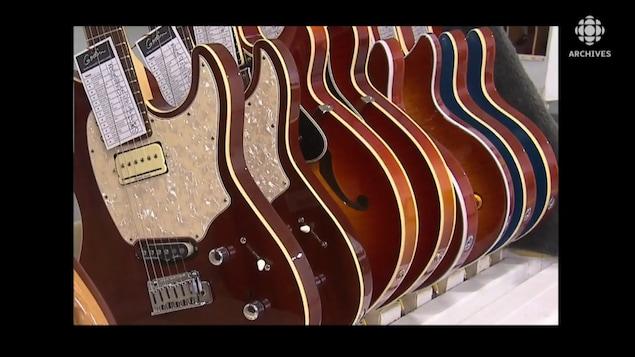 Guitares électriques alignées sur un présentoir.