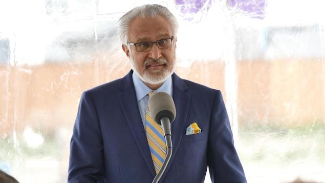 Gulzar Cheema est devant un podium et dans une tente blanche située à l'extérieur.