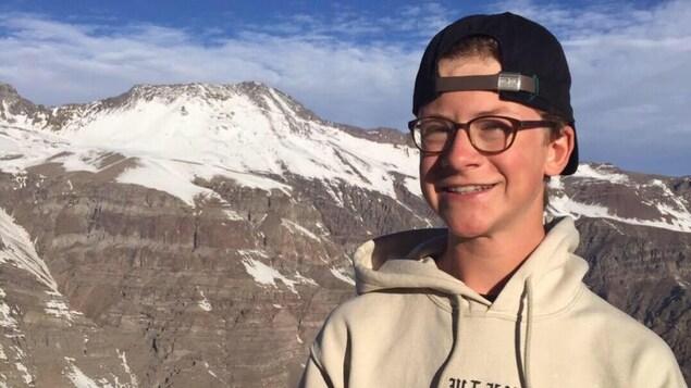Gustave Bouchard, 15 ans, a lancé une pétition pour l'aménagement de pistes de vélo de montagne au Mont-Orford. On le voit ici posé devant des montagnes, au Chili.