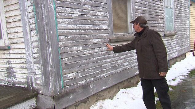 M. Vézina touche la maison de ses doigts.