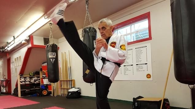 Un homme effectue un coup de pied vers le haut. Il porte un habit de karaté ainsi que sa ceinture noire.