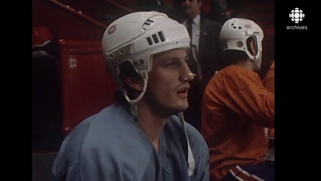 Plan buste de Guy Carbonneau, assis sur le banc des joueurs, qui porte un casque avec une visière.