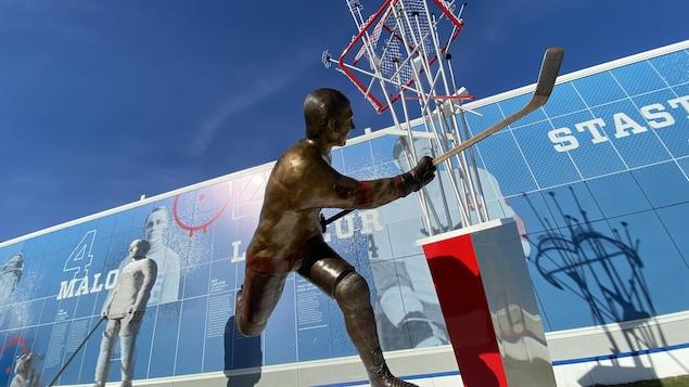 Devant une statue de bronze de Guy Laleur, une trainée de rondelle défoncent un filet accroché dans les airs.
