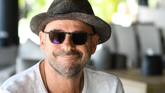 Il porte des lunettes fumées et un chapeau. Il sourit.