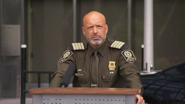 Guy Lapointe, en uniforme de la SQ, devant un lutrin, regarde devant lui.