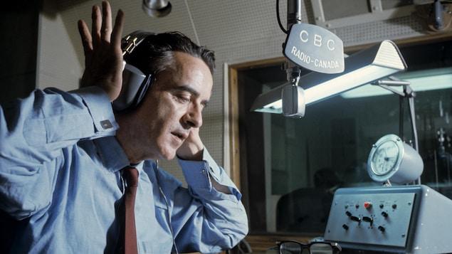 Dans un studio de radio, assis à une table, l'animateur Guy Mauffette enfile les écouteurs sur ses oreilles.