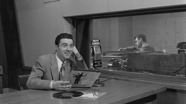 Guy Mauffette, en studio radio, souriant, un vinyle à la main.