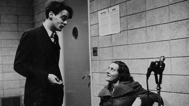 Dans un studio de radio, le réalisateur Guy Mauffette discute avec une femme.