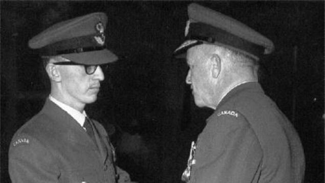 Un homme reçoit son diplôme. Les deux hommes portent l'uniforme.