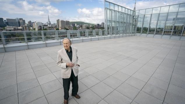 Guy Rocher debout sur la terrasse de la Nouvelle Maison de Radio-Canada.