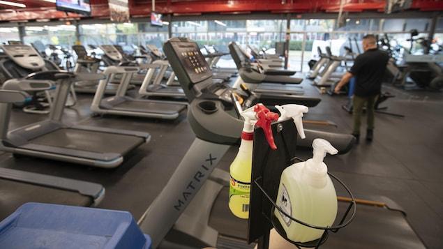 Des produits désinfectants sont disposés près de machines d'exercice.