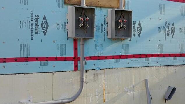 Sur un mur de maison non fini, des boîtes électriques ne contiennent plus de fils.