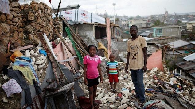 Un père, sa fillette et son fils dans les décombres d'une maison.