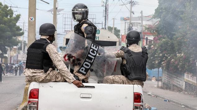 Des policiers sont assis à l'arrière d'une camionnette dans les rues de la capitale haïtienne.