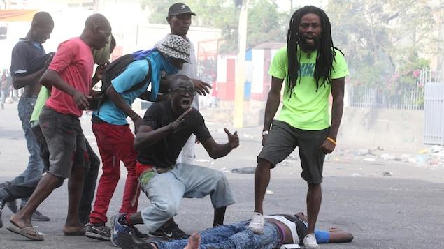 Réactions de citoyens aux côtés du corps d'un des leurs durant une manifestation contre le gouvernement à Port-au-Prince.