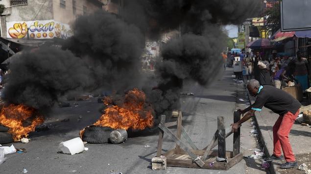 Un homme bloque une rue de Port-au-Prince en Haïti, alors que des pneus brûlent et dégagent une dense fumée noire.